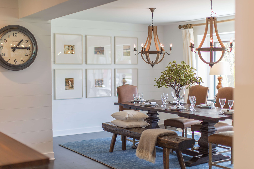 Formal rustic dining room with wood dining bench, double chandeliers and symmetrical gallery wall