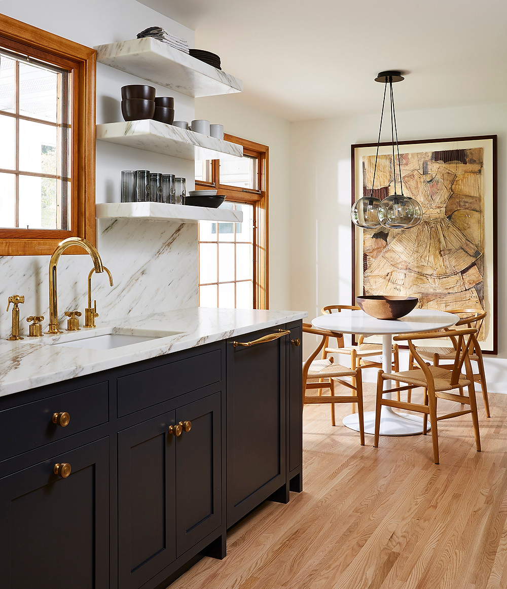 Luxury small space kitchen with marble countertops, shelves, unlacquered brass sink faucet, dark blue cabinetry and refinished hardwood floors next to small dining nook