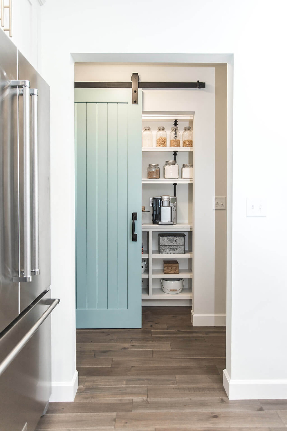 Beautiful turquoise blue barn dark leading to step-in pantry which used to be a hall closet