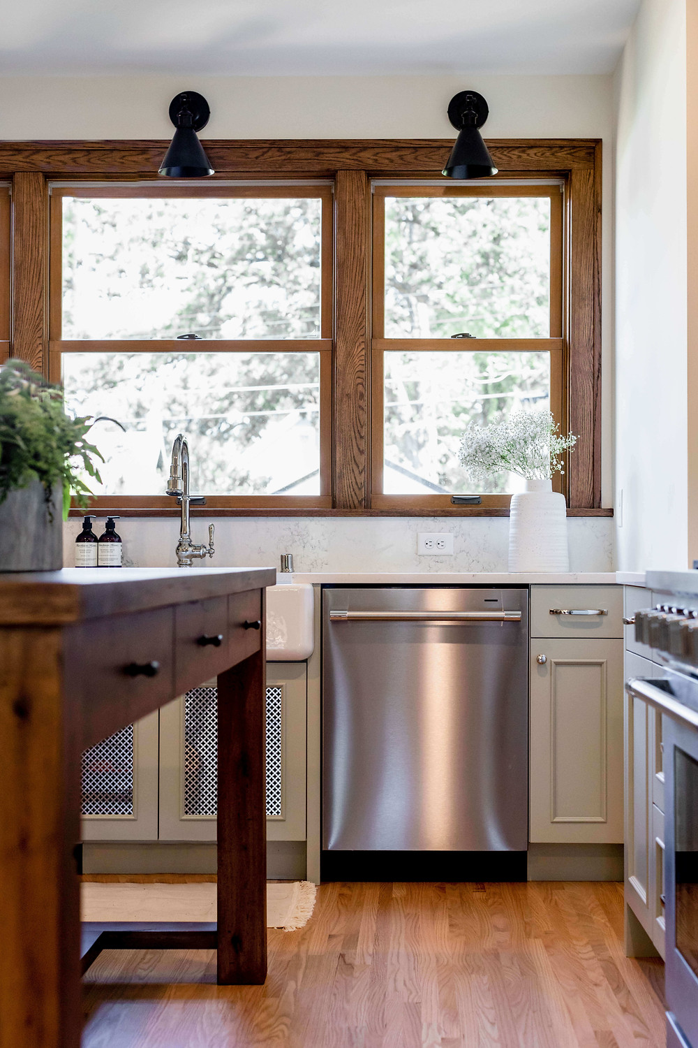 Tudor style kitchen renovation with custom craftsman baker's table and beautiful wood window trim