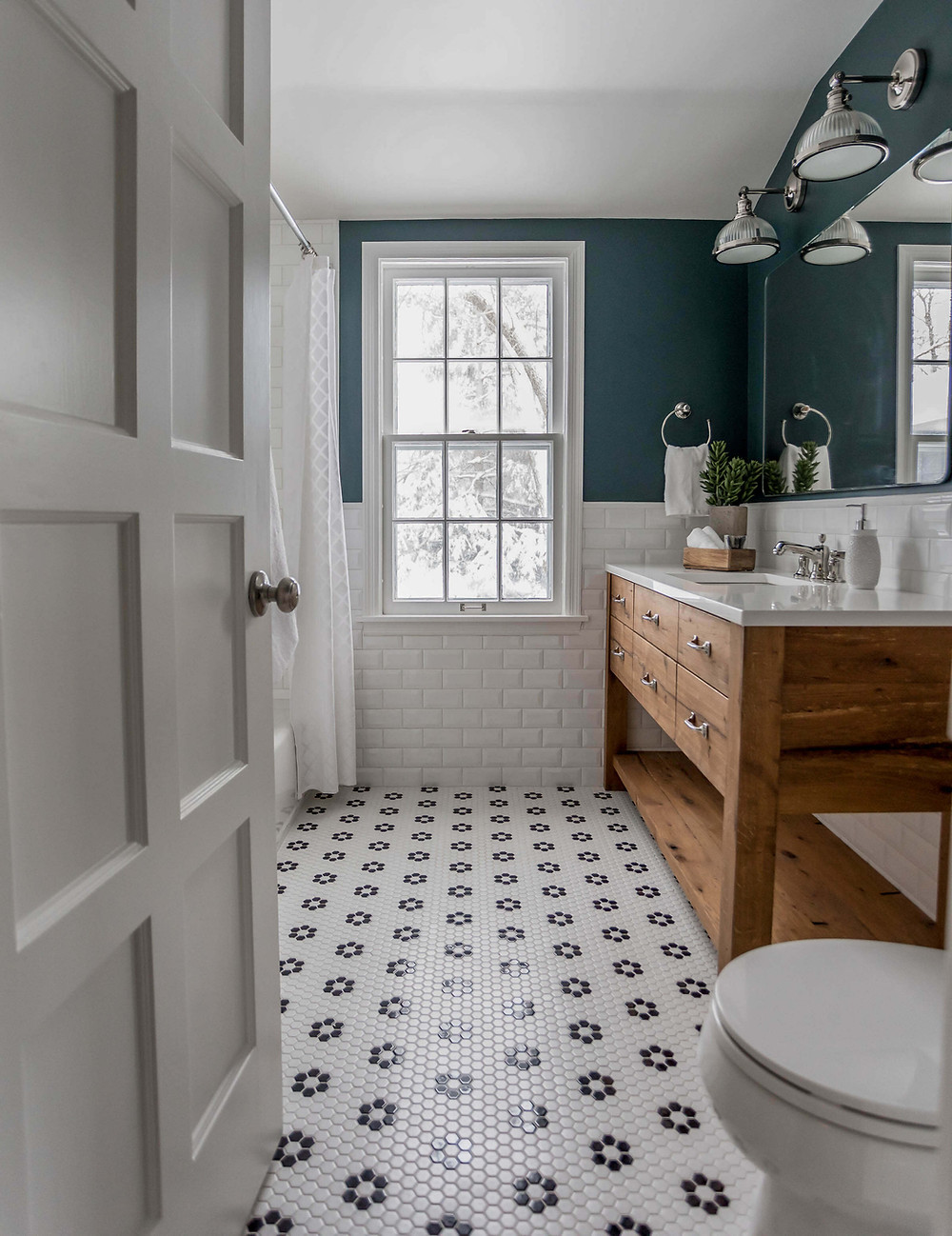 Flower pattern penny floor tile bathroom with reclaimed wood vanity and bold teal walls above a half wall of subway tile