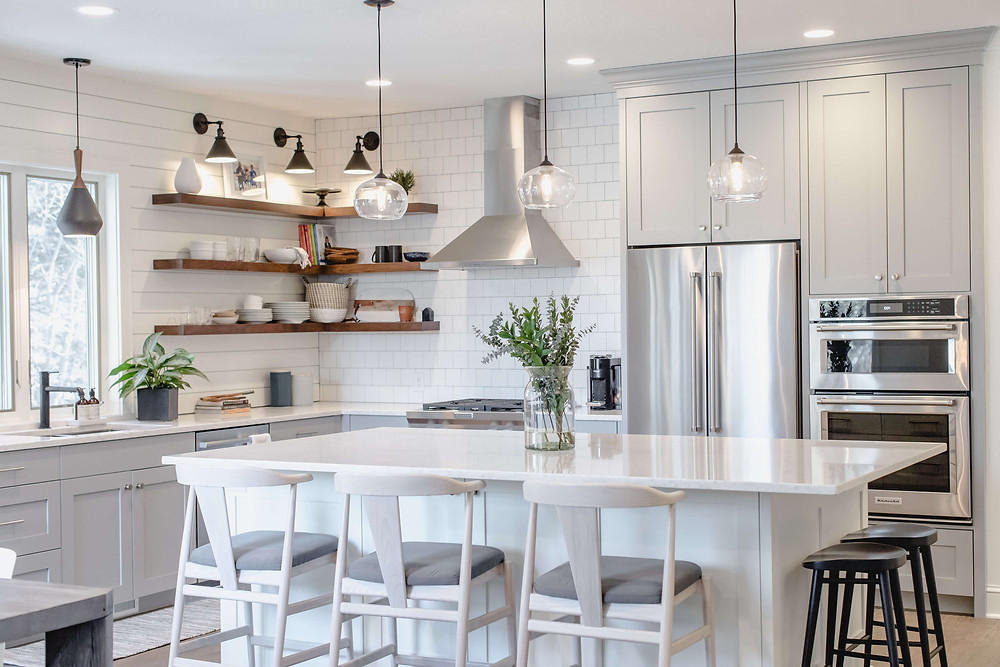 Bright custom kitchen with light grey cabinetry, white island and L shaped walnut floating shelves in the corner by the range hood, mixing horizontal shiplap and white square tile backsplash