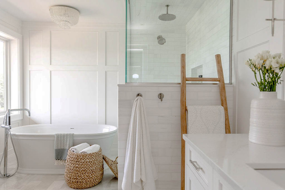Glamorous en suite bathroom with custom millwork and marble details with freestanding bathtub