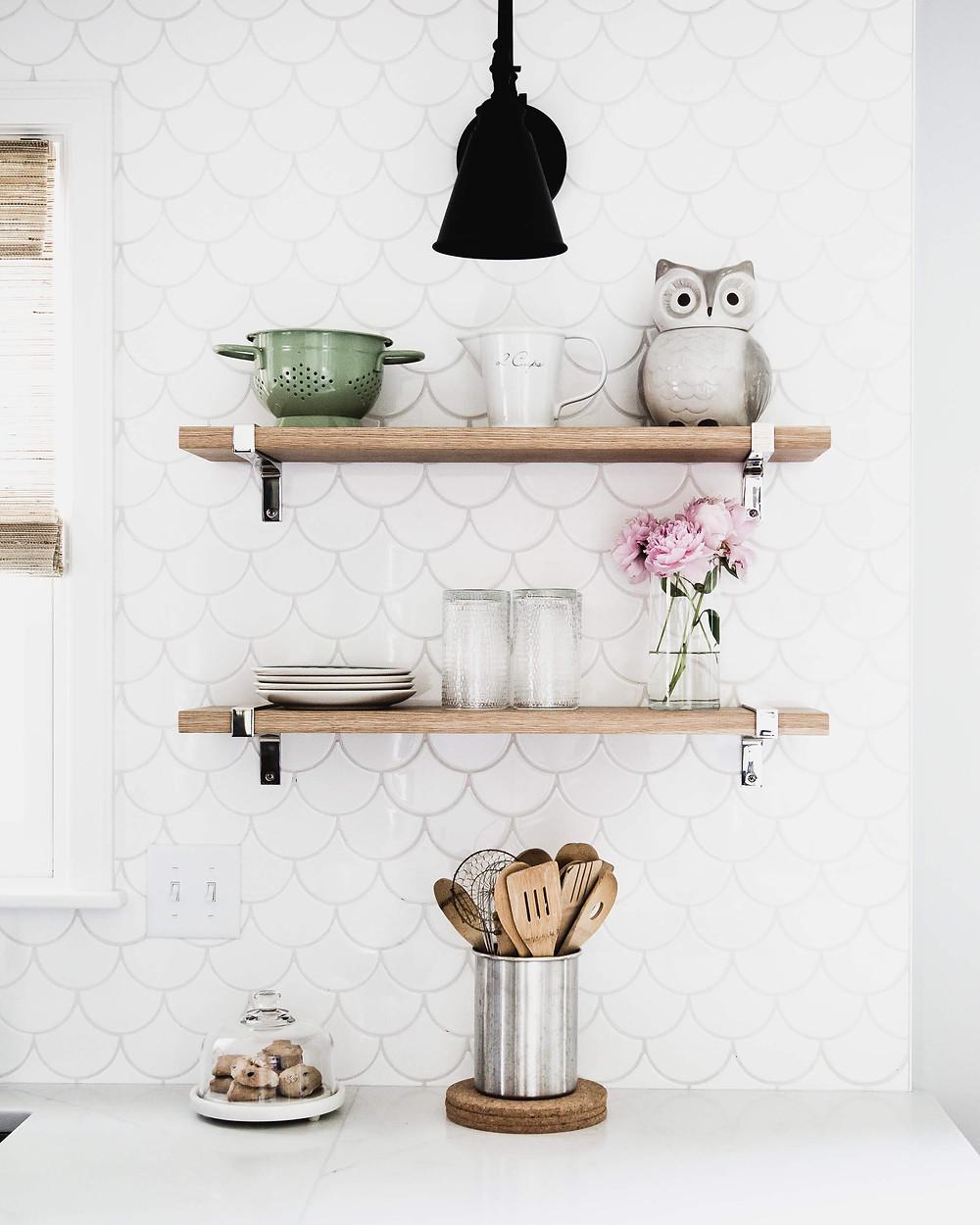 Delicate fish scale tile backsplash, white oak floating shelves and black arm sconce