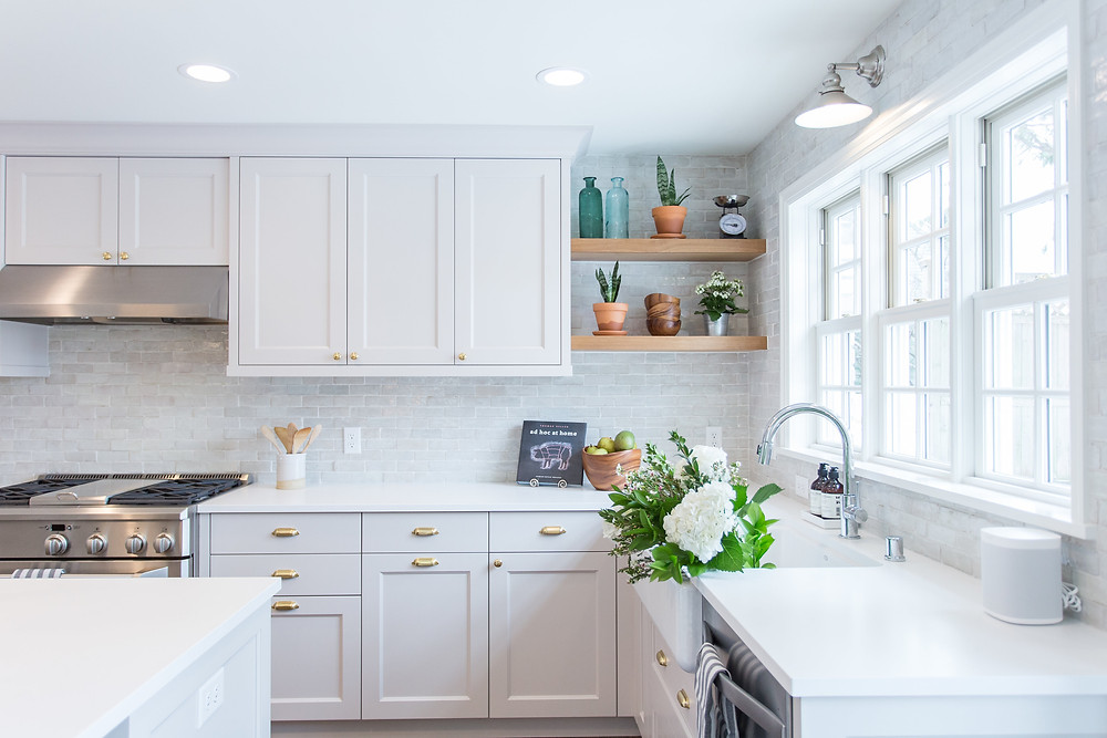 Charming city kitchen with a wall of beautiful windows over a farmhouse sink and artisan backsplash tile