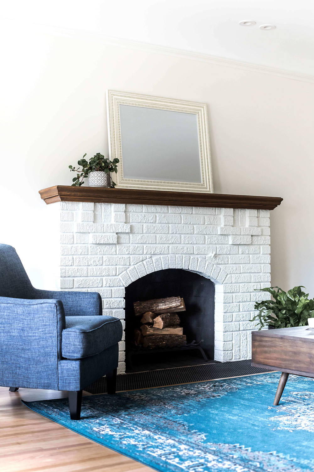 Tudor style living room with painted white brick fireplace, stained oak mantel and blue furnishings