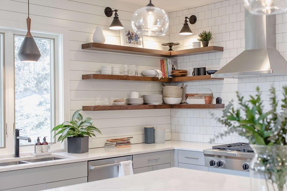 Charming kitchen renovation mixing square  tile with horizontal shiplap backsplash with walnut corner floating shelves
