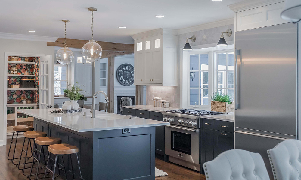 Two-tone kitchen cabinetry with dark blue lower cabinets, island and white uppers with charming wallpaper pantry and reclaimed white oak beams and posts