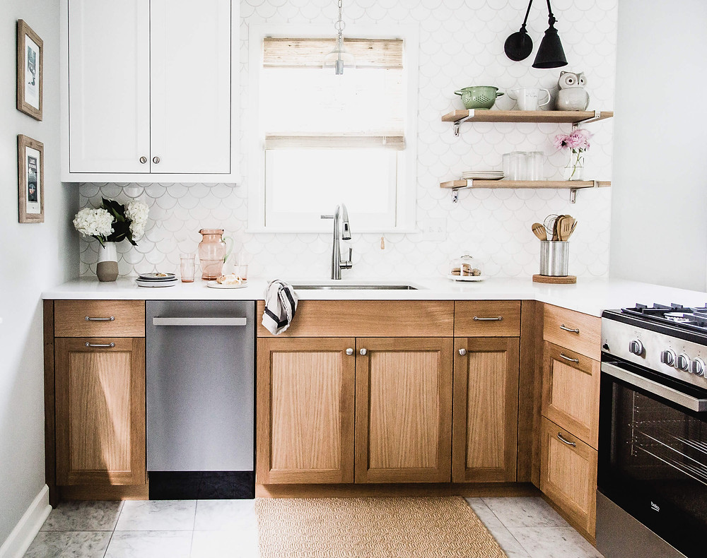 White upper cabinets grounded by custom white oak base cabinets with playful fish scale tile backsplash and floating shelves