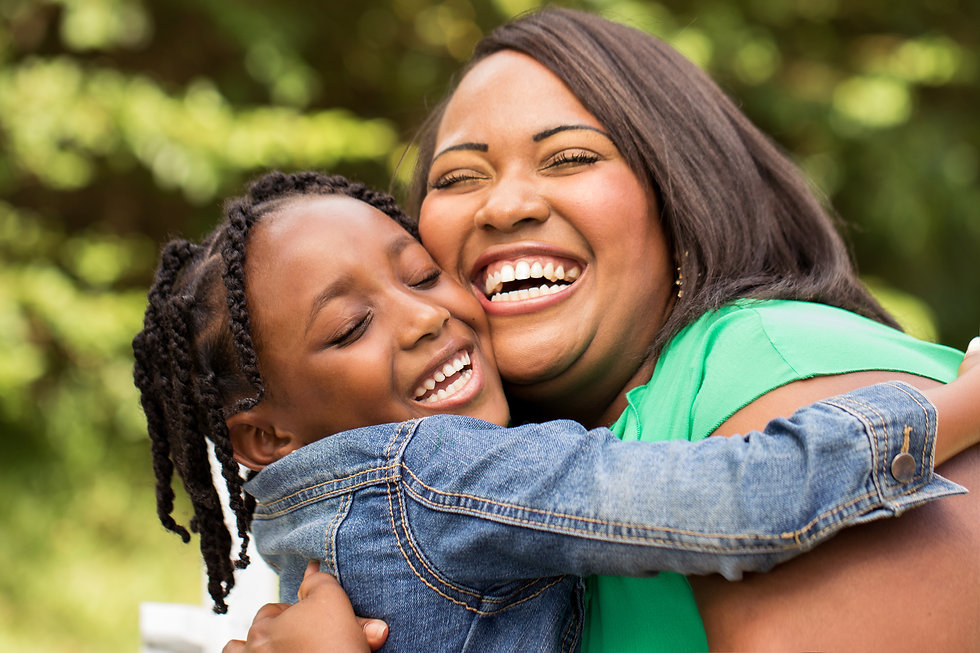 Black woman and young daughter smiling while embracing, outside in nature.