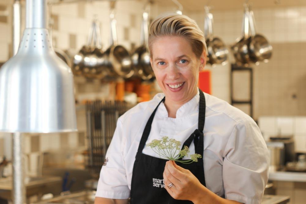 Mari Wigren står i ett restaurangkök och ler mot kameran
