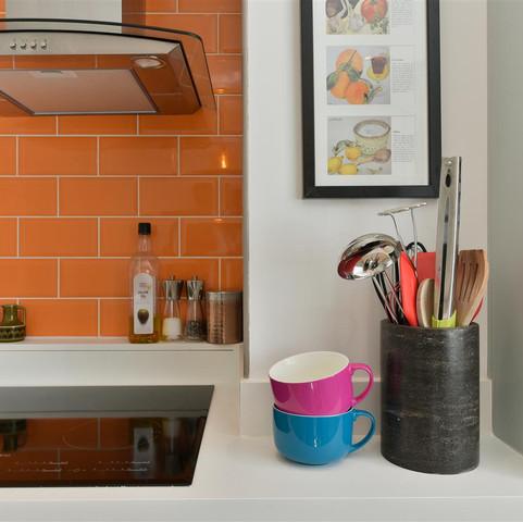 Kitchen with orange tiled splashback