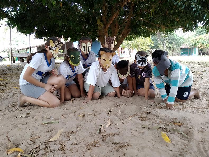PraCegoVer Foto de crianças agachadas na areia usando máscaras de jaguatirica, lagarto, quati, onça parda, tatu-canastra, queixada, guaxinim e anta.