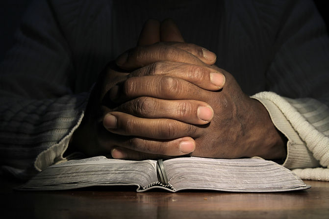 man praying with the bible on black background stock photo.jpg