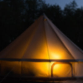 Traditional bell tent glows at night at