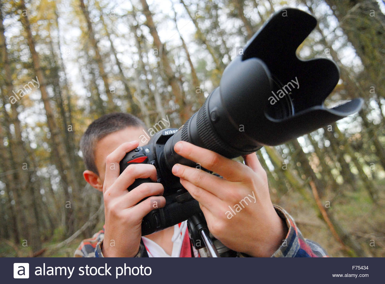 teenage-boy-with-dslr-camera-in-forest-F