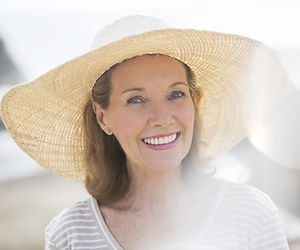 Older woman wearing straw hat on beach