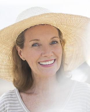Oudere vrouw met strooien hoed op het st