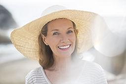 ビーチでわら帽子を身に着けている年上の女性