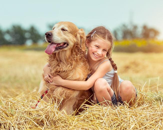 happy little girl with her dog golden retriever in rural areas in summer.jpg