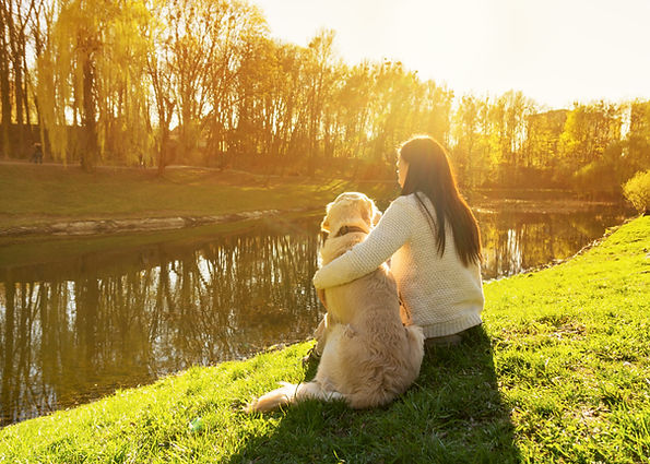 Young woman and golden retriever dog sit