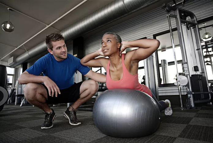 A Personal Trainer instructing their client on a Swiss ball