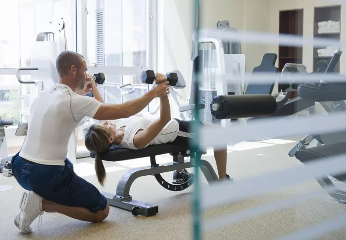 PT guides a client through an exercise