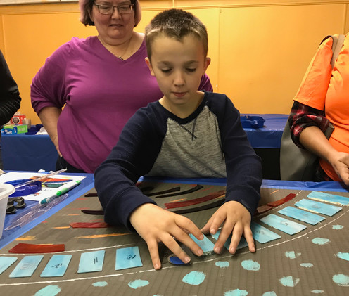 Community art making session inside of the NAC space! This young man was helping to create the mosaic that adorns the outside of the NAC facility!