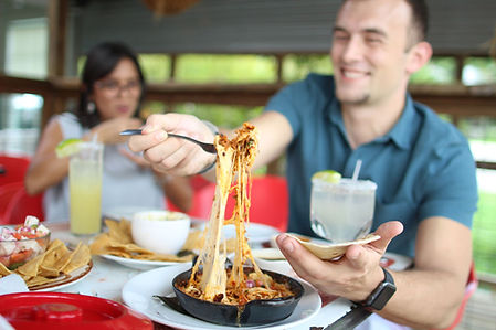 Couple enjoying happy hour on the patio with a cheese pull from the queso flameado