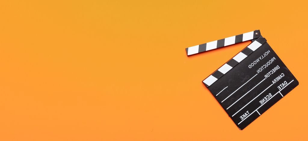 movie-clapperboard-on-orange-color-backg