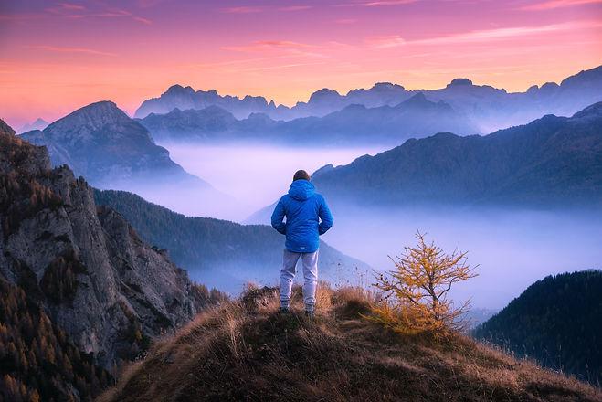 Sporty man on the mountain peak looking