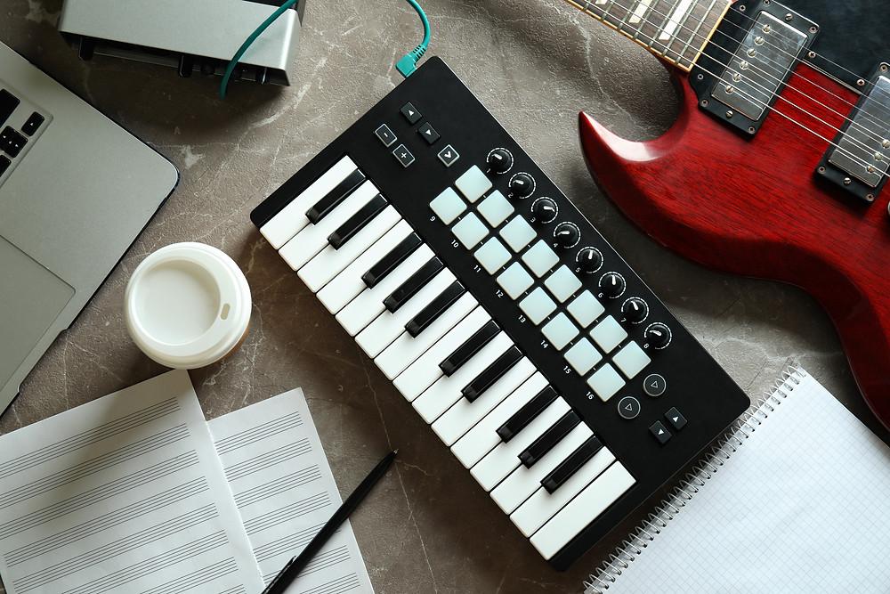 table avec piano, guitare, ordinateur, partitions pour faire de la musique