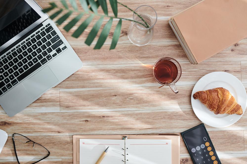 bureau de travail avec ordinateur, cahier, thé et croissant