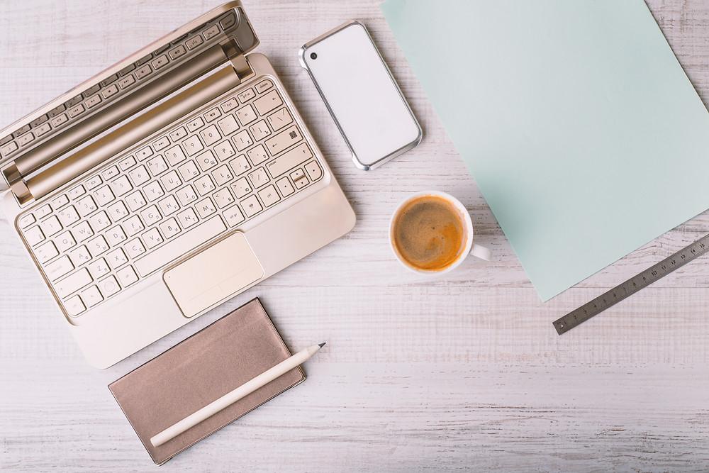ordinateur rose avec notebook et téléphone dans une ambiance sereine