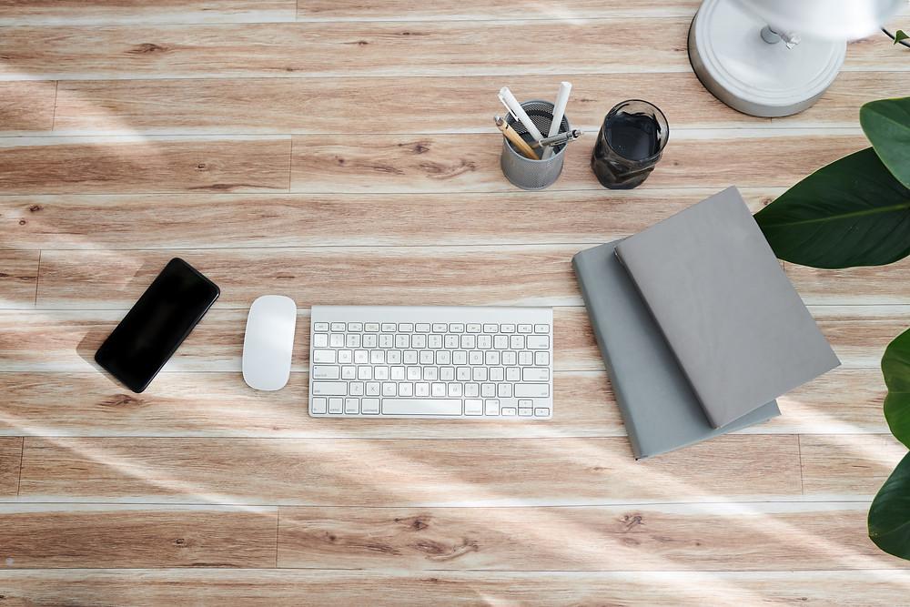 clavier ordinateur avec cahiers, stylos, un téléphone et une plante verte