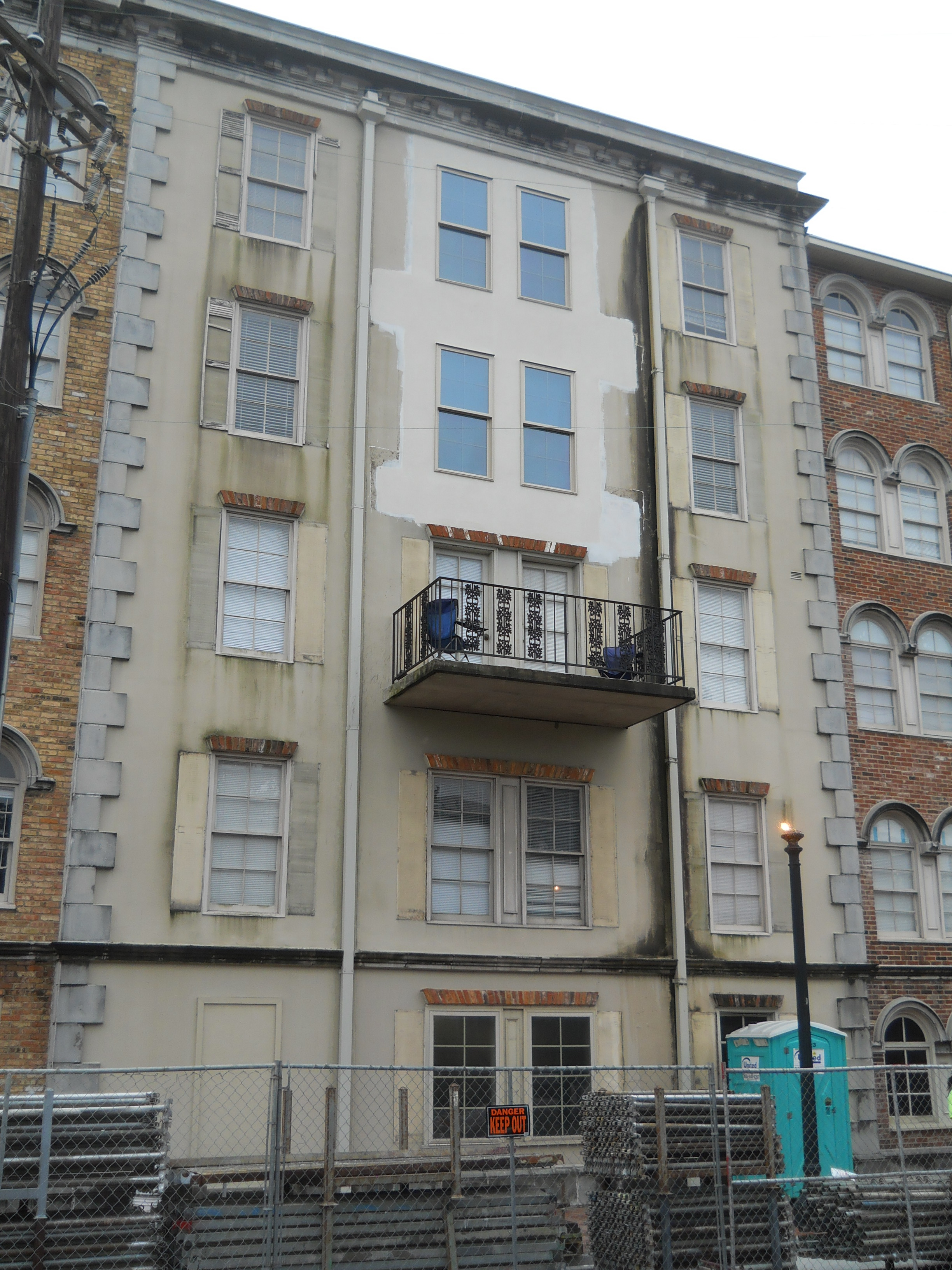 Removed balconies with repaired stucco and replacement windows before painting