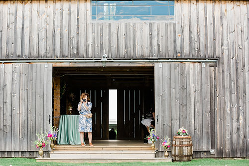 Darcy stands in barn doorway with camera to her eye.