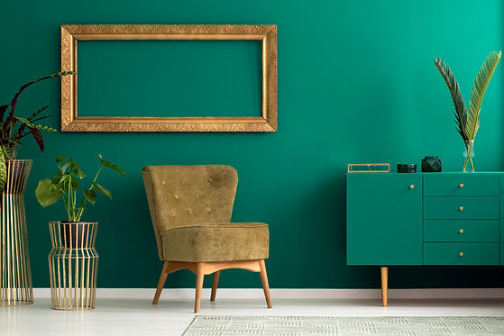 Palm leaf on a modern, teal sideboard wi