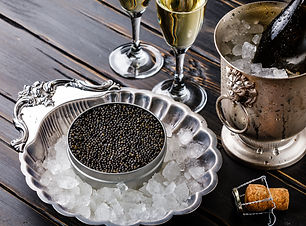 Black caviar in can on ice in silver bow