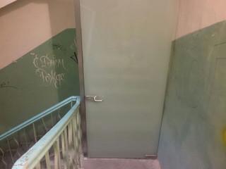 Стеклянная дверь в портале из нержавейки