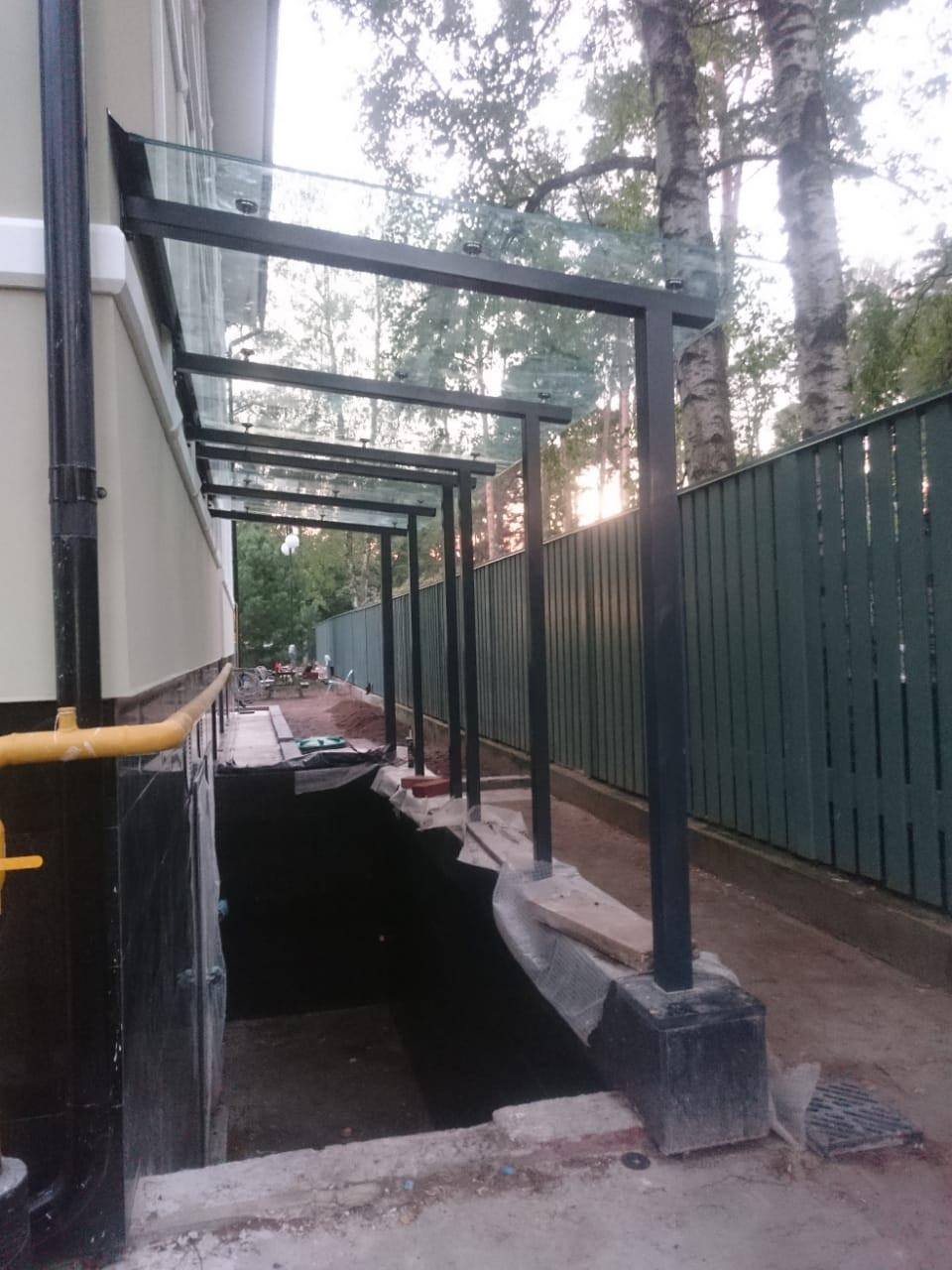 Стеклянный навес на металлических столбах