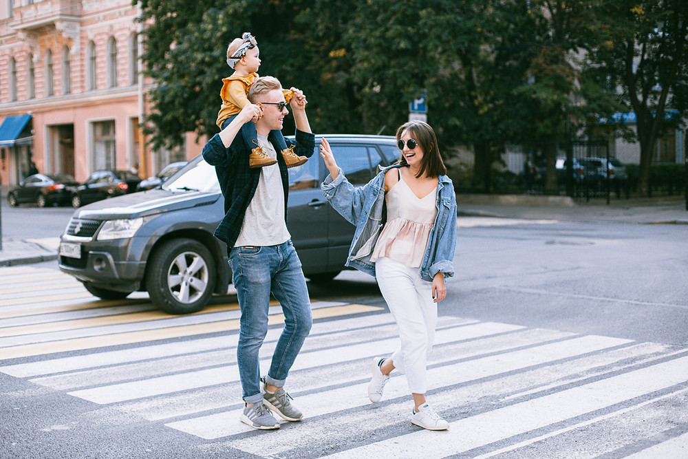 man carrying baby on his shoulders with girlfriend next to him