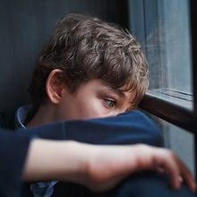 Teenage boy staring out of window looking sad and alone