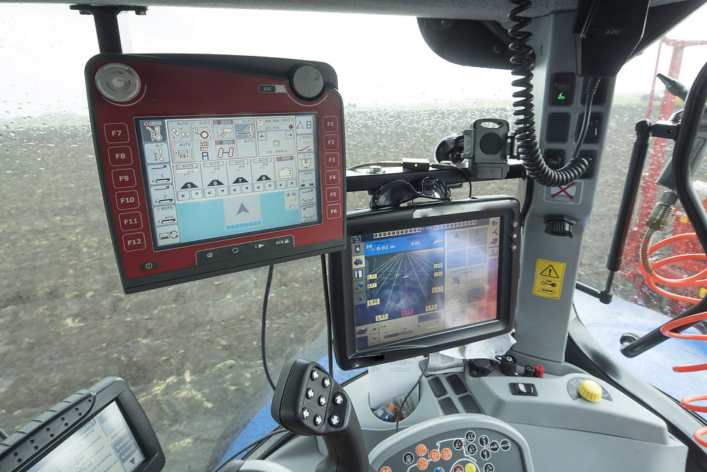 Tracker with three screens and multiple buttons makes its way through a rainy field.