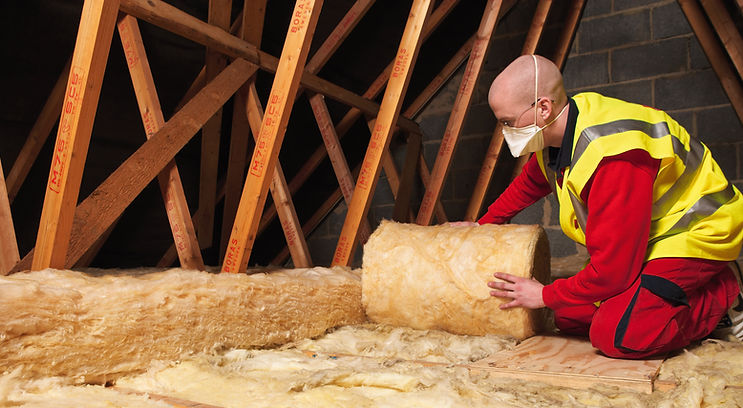 An image of a man installing mineral fibre loft insulation. Healthy Homes Dorset provide grants for this type of insulation.