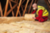 An image of a man installing mineral fibre loft insulation.
