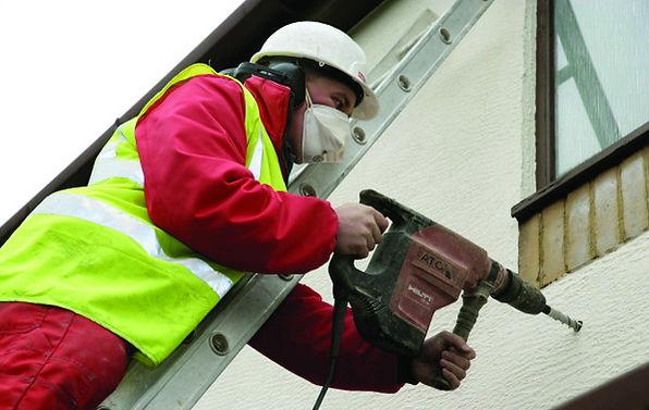 An image of a man installing cavity wall insulation. Healthy Homes Dorset provide grants for this type of insulation.