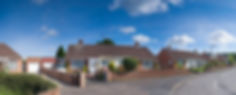 An image of a bungalow on a sunny street. This house could have cavity wall insulation installed.