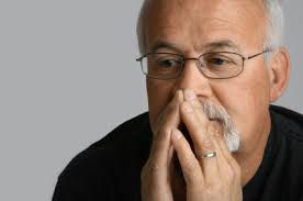 Pictue of a man with goatee and grey hair looking pensive