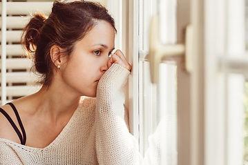 anxious woman looking through window